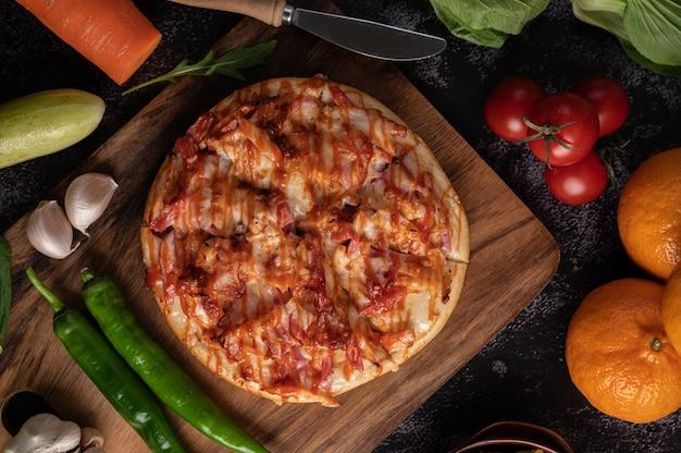 Pizza com linguiça, milho, feijão, camarão e bacon em prato de madeira
