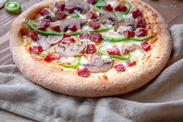 Pizza com linguiça picada, cogumelos e pimenta verde em um pedaço de toalha de mesa
