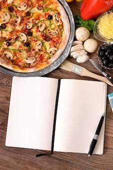 Pizza com livro de receitas em branco e ingredientes