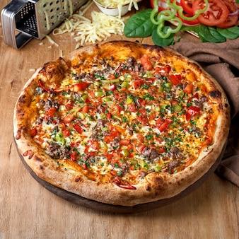Pizza com molho de tomate carne tomate cebola roxa e queijo no fundo de madeira