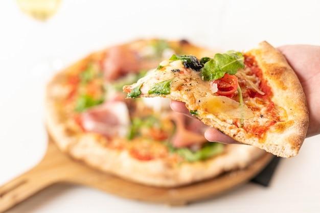 Pizza com mussarela e presunto cru, servido em uma placa