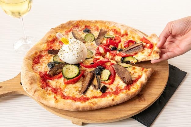 Pizza com mussarela e vegetais servida em tabuleiro