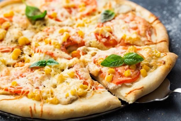 Pizza com pedaços de carne de frango, tomate, milho e queijo