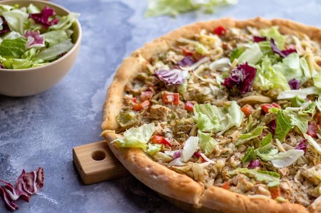 Pizza com peito de frango churrasco tomate e ervas em uma placa de madeira