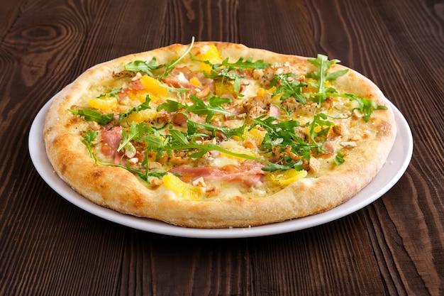 Pizza com peru, bacon, laranja e castanha de caju na mesa de madeira escura
