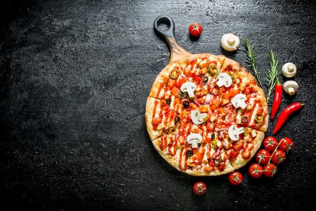 Pizza com pimenta, tomate e cogumelos na mesa rústica preta