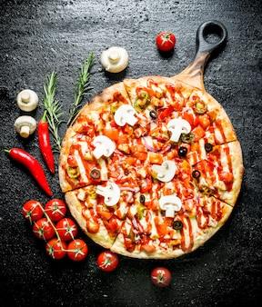 Pizza com pimenta, tomate e cogumelos na mesa rústica preta.