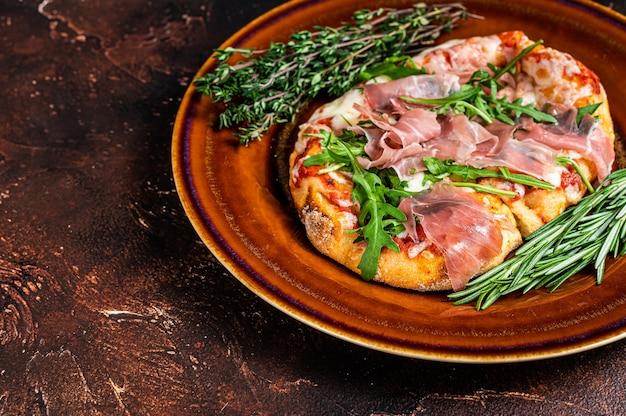 Pizza com presunto de parma prosciutto, salada de rúcula e queijo parmesão em prato rústico. fundo de madeira. vista do topo. copie o espaço.