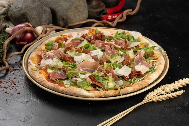 Pizza com presunto de parma, queijo parmesão, tomate seco e rúcula