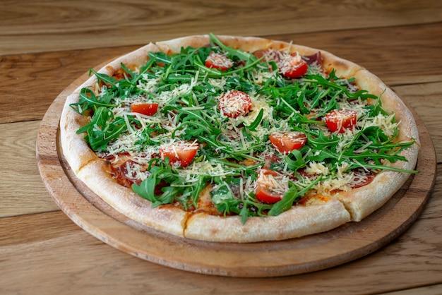 Pizza com presunto de parma, salada de aurugula, tomate cereja e parmesão na placa de madeira