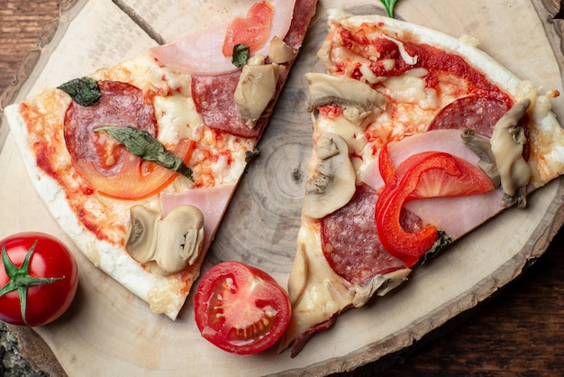 Pizza com presunto e bacon, cogumelos e tomate em uma fatia de madeira em um fundo de madeira marrom.