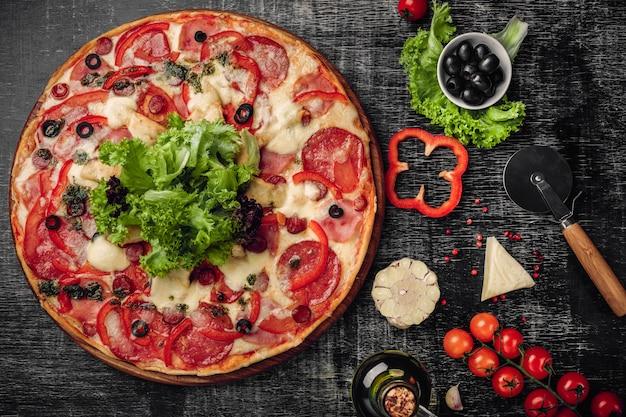 Pizza com presunto, salame, queijo, cogumelos, tomate cereja, pimentão e salada em um quadro de giz preto.