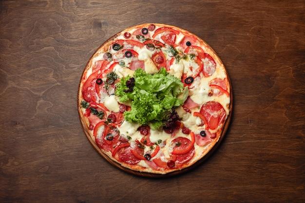 Pizza com presunto, salame, queijo, cogumelos, tomate cereja, pimentão e salada em uma placa de madeira marrom.