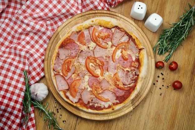 Pizza com presunto, salame, queijo derretido e tomate em uma bandeja de madeira. pizza em composição com ingredientes em uma mesa de madeira. vista superior, espaço de cópia