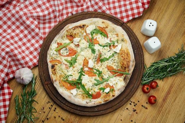 Pizza com quatro tipos de queijo, rúcula e tomate em uma bandeja de madeira. pizza em composição com ingredientes em uma mesa de madeira