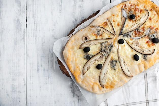 Pizza com queijo brie e berinjela em um fundo branco de madeira.