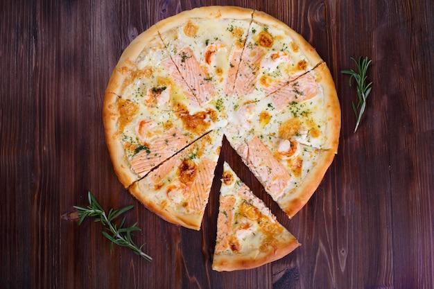 Pizza com queijo carne pimentas e tomates na madeira