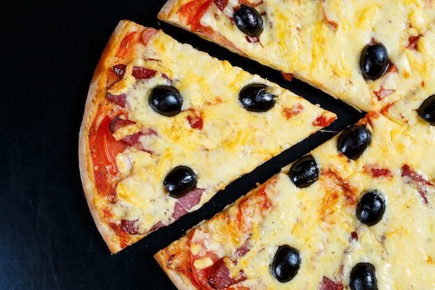 Pizza com queijo e molho de tomate, azeitonas, mussarela fresca, parmesão e manjericão e carne em fundo escuro