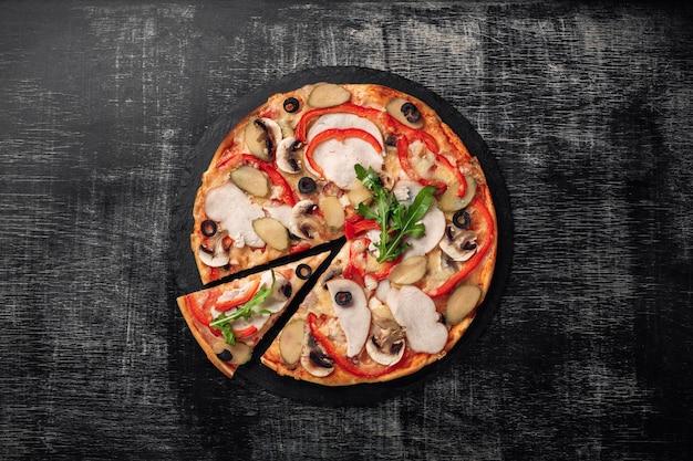 Pizza com queijo, presunto, pepinos em conserva, carne e azeitonas na placa de giz.