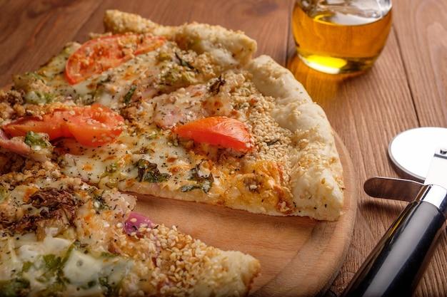 Pizza com queijo, tomate, presunto e sementes de gergelim em uma tábua