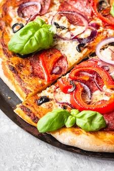 Pizza com salame, cebola, pimenta, azeitonas, mussarela e manjericão. pizza de pepperoni quente caseira.