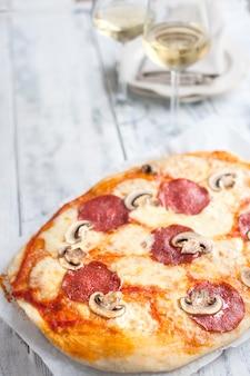 Pizza com salame e cogumelos e dois copos de vinho branco