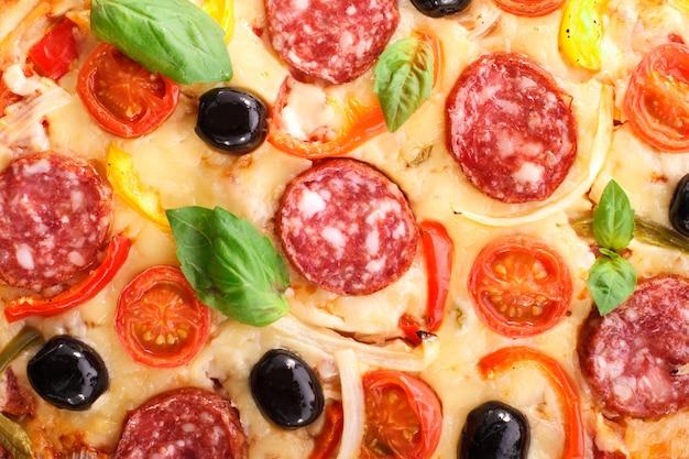 Pizza com salame e legumes em um fundo de madeira velho.