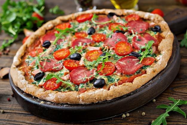 Pizza com salame, tomate, azeitona e queijo em uma massa com farinha de trigo integral. comida italiana.