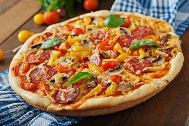 Pizza com salame, tomate, queijo e cogumelos