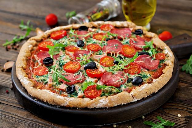 Pizza com salame, tomates, azeitonas e queijo em uma massa de pão com farinha de trigo integral. comida italiana.