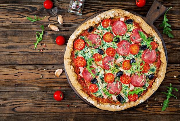 Pizza com salame, tomates, azeitonas e queijo em uma massa de pão com farinha de trigo integral. top vie