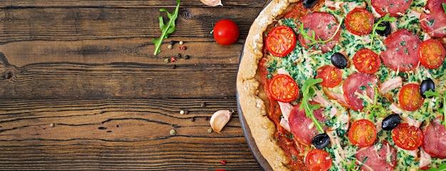 Pizza com salame, tomates, azeitonas e queijo em uma massa de pão com farinha de trigo integral. vista do topo
