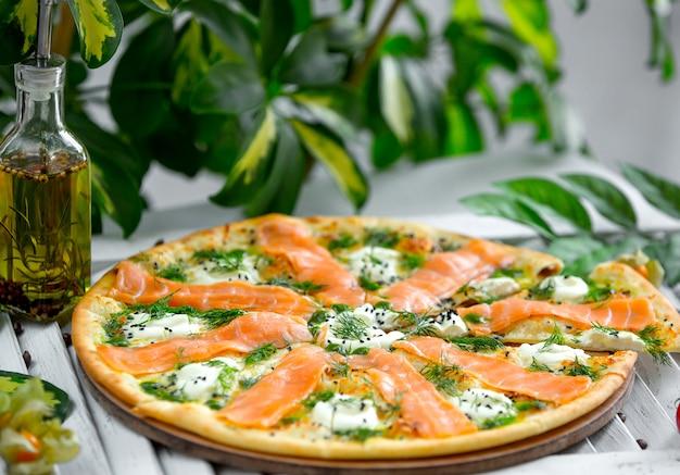 Pizza com salmão e mussarela em cima da mesa