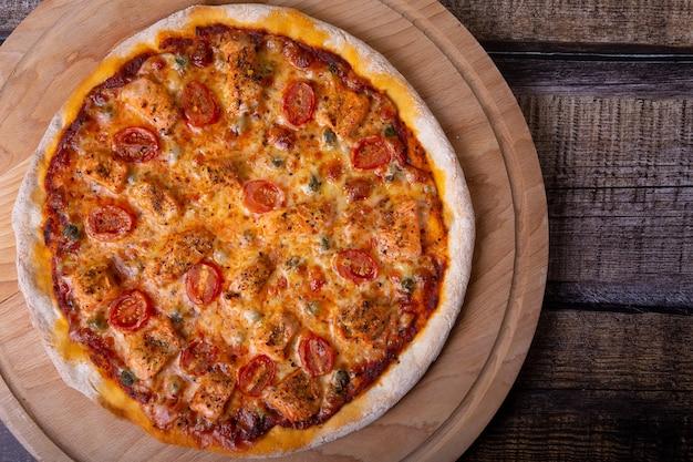 Pizza com salmão, tomate e alcaparras em uma placa de madeira. pizza inteira.
