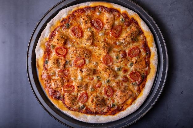Pizza com salmão, tomate e alcaparras. pizza inteira em um fundo preto.