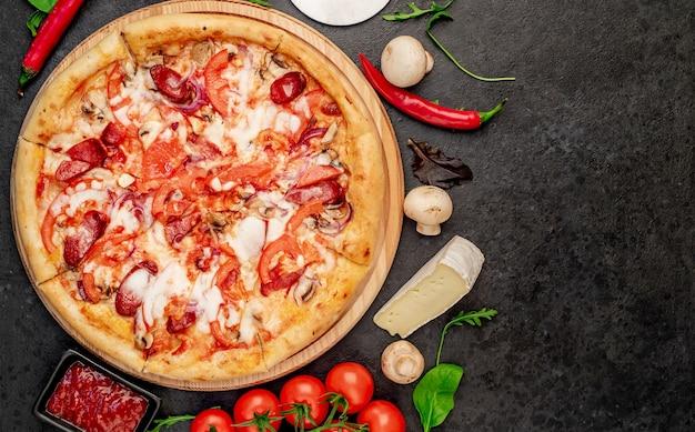 Pizza com salsichas cogumelos, tomate e queijo em um fundo de pedra com espaço de cópia para o seu Foto Premium