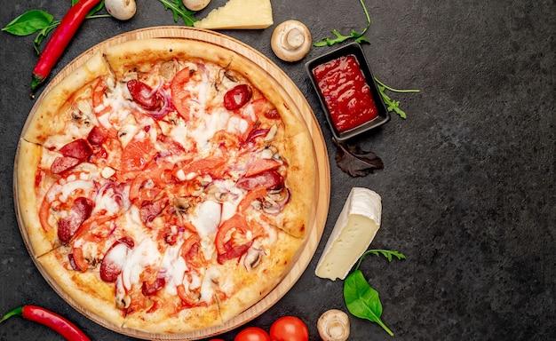 Pizza com salsichas cogumelos, tomate e queijo em um fundo de pedra com espaço de cópia para o seu
