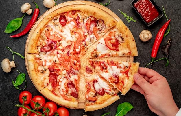 Pizza com salsichas cogumelos tomate e queijo sobre um fundo de pedra