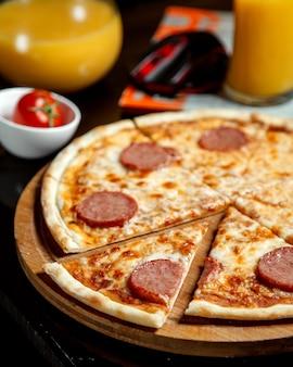 Pizza com salsichas fatiadas e suco de laranja