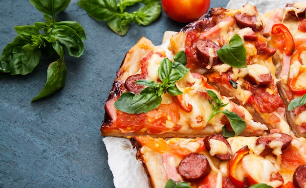 Pizza com salsichas, legumes e queijo cortado em fatias close-up