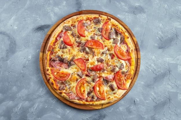 Pizza com tomate, bacon, carne e queijo em um fundo cinza