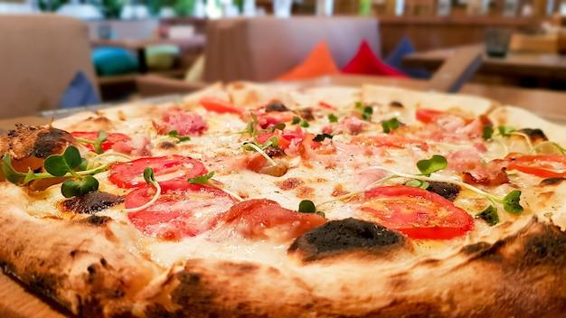 Pizza com tomate, carne e bacon no fundo de um café na mesa.