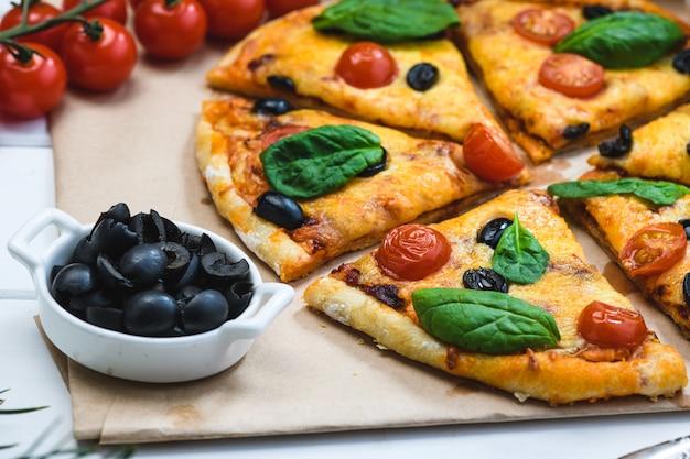 Pizza com tomate e espinafre em um fundo branco e ramos de abeto de natal