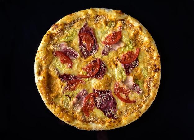 Pizza com tomate, fiambre e queijo numa mesa de madeira