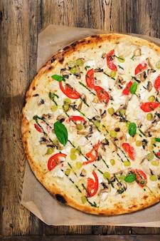 Pizza com tomate, mussarela, cogumelos e pesto de manjericão. pizza