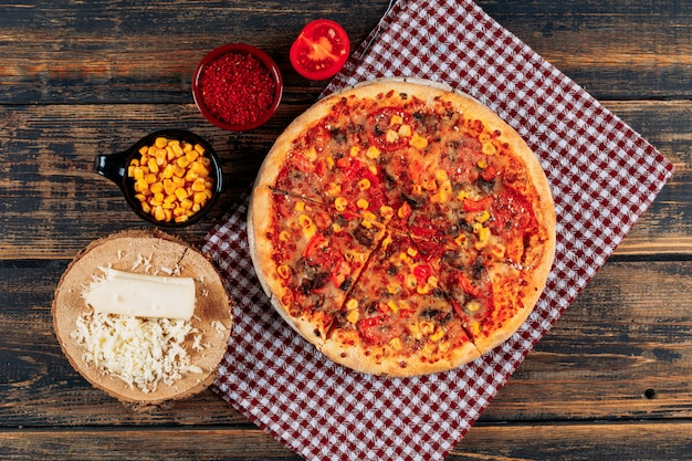 Pizza com uma fatia de tomate, uma barra de especiarias e milho, queijo a granel no fundo escuro de madeira e piquenique pano, close-up.