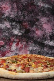 Pizza cozida de ingredientes mistos com fatias de calabresa.