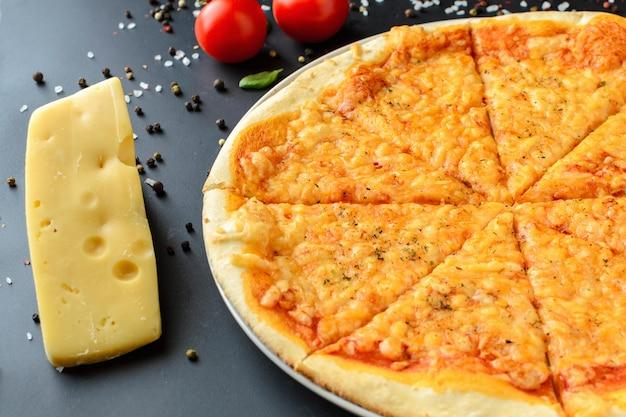 Pizza cozida em um fundo escuro com ingredientes