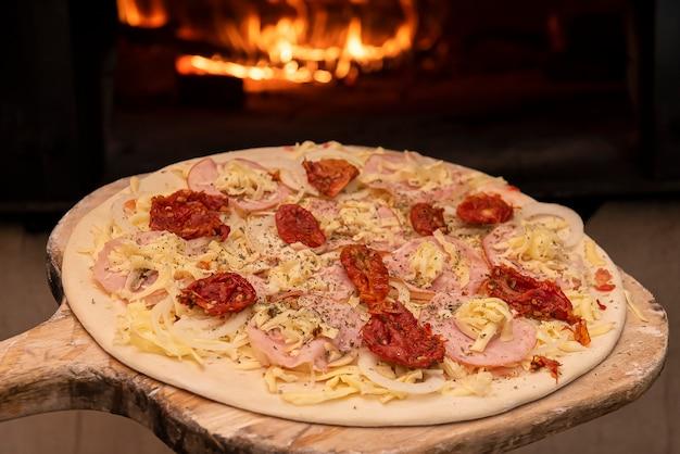 Pizza crua ao estilo brasileiro entrando no forno a lenha. foco seletivo
