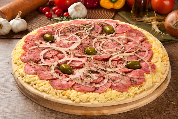 Pizza crua com calabresa em espaço de madeira